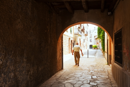 breda:  Old street with arch in  European town. Breda, Catalonia Stock Photo