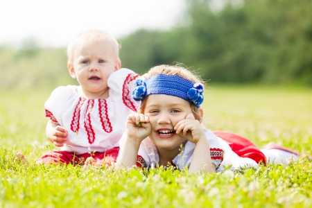 Two children in traditional folk clothes on grass meadow photo