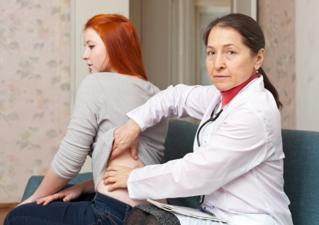 Mature physician touching  behind of female patient  in interior. Focus on  doctor photo