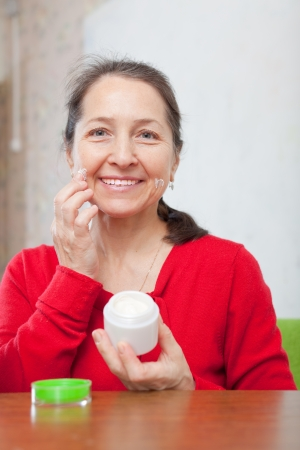 Happy mature woman in red dress puts cream on face at home interior photo