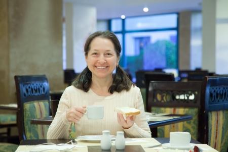 morning tea: Woman having breakfast in hotel restaurant Stock Photo