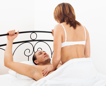 Man and woman having sex on white sheet photo
