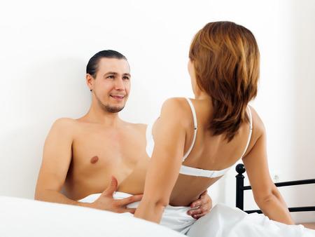 Hombre hermoso que tiene relaciones sexuales con una mujer en la cama. Centrarse en hombre photo