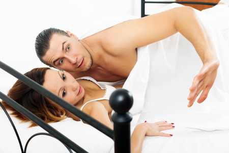 emotional middle-aged couple caught during adultery  in bed  photo