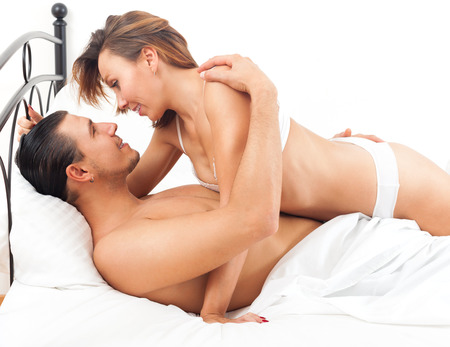 Smiling adult couple having sex on bed in bedroom interior at home photo
