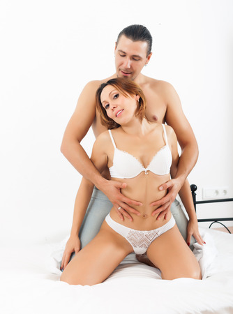 Handsome man playing with woman in underwear at bedroom photo