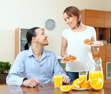 serves: Smiling woman serves breakfast her beloved husband in morning
