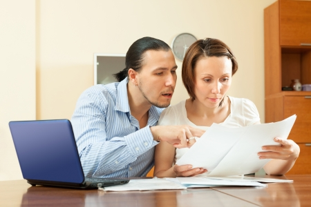 couple staring financial documents at table in home photo