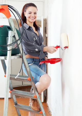 Happy girl  on stepladder paints wall with roller at home photo