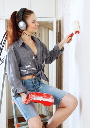 girl in headphones  makes repairs in the apartment photo