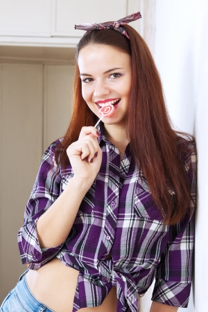 sucking lollipop:  Pretty young housewife sucking lollipop in home Stock Photo