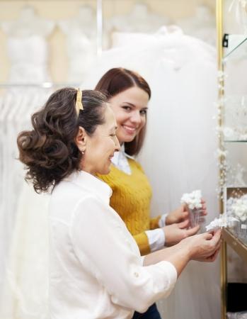 women  chooses bridal accessories at shop of wedding fashion photo