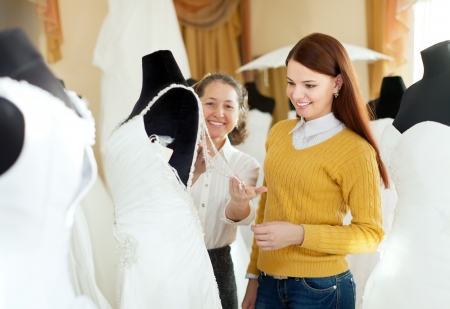 wedding gown: pretty bride chooses bridal outfit at wedding store. Shop consultant helps her