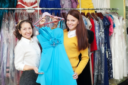 Two women chooses evening dress at fashion store photo