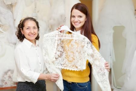 Happy mature bridesmaid with bride chooses bridal clothes at shop of wedding fashion photo