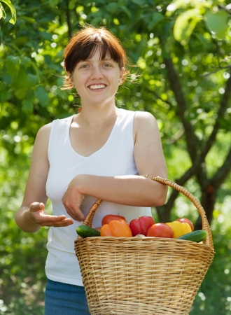 Happy young woman with basket of harvested vegetables in garden photo