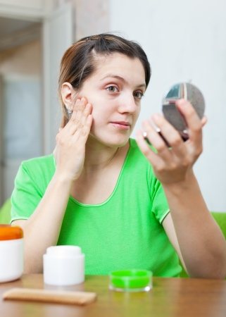 woman  in green  stares on her skin in mirror at home photo