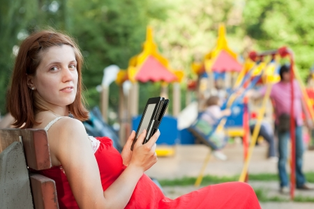 gravida:  pregnancy woman reads e-book against  playground area Stock Photo