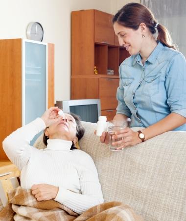 nasal drops: Senior woman dripping nasal drops. Adult daughter takes care of her at home