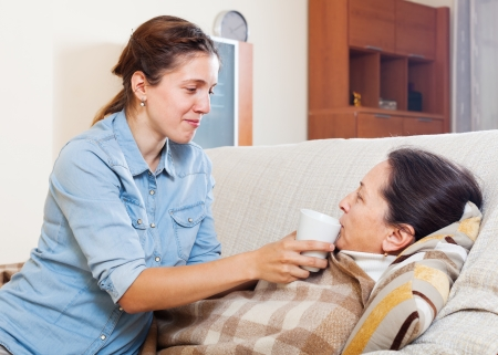 Adult woman caring for sick mature mother in living room photo