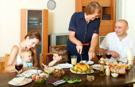 celebratory: Portrait of happy smiling multigeneration family communicate over holiday table at home interior