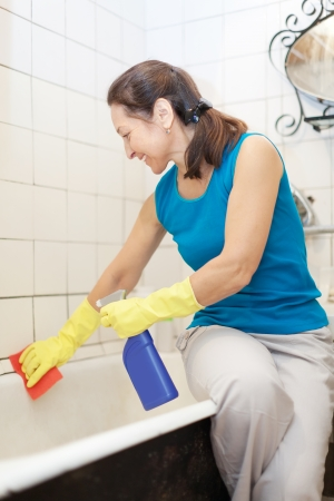 Smiling mature woman cleans bathtub with rug and cleaner in bathroom at her home photo