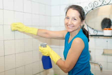mature woman cleans bathroom with bottle of cleaner  photo