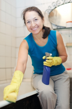 Smiling mature woman cleans bathroom with sponge and cleaner at her home photo