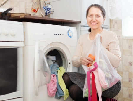mature housewife loading the washing machine in kitchen photo