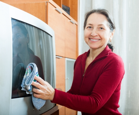 Happy mature woman dusting TV  photo