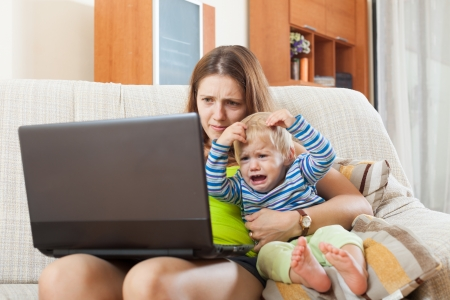 malcontent: sorehead mother with crying baby working online with laptop at home