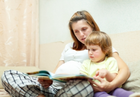 Mother and child reading  book together on couch in home. Focus on woman photo
