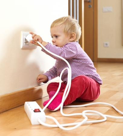 riskiness: Adorable toddler playing with electricity at home Stock Photo