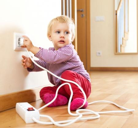 descarga electrica: Ni�o que juega con el equipo el�ctrico en el hogar