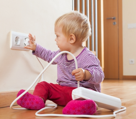 jeopardy: Toddler playing with electricity at home Stock Photo
