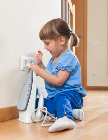 riskiness: three year old baby playing with electric iron on floor at home