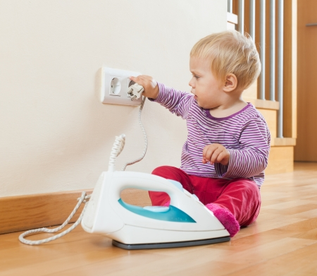 Toddler  playing with electric iron at home photo