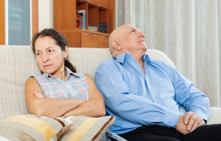 Family quarrel. Mature woman having conflict with her senior man in living room  photo