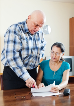 Mature couple fills in questionnaire together at home interior. Focus on man photo