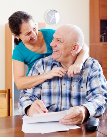 calculated: Happy  mature couple fills in paper documents together at home