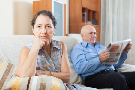 couple married: Portrait of sad mature woman against elderly man with newspaper in home interior