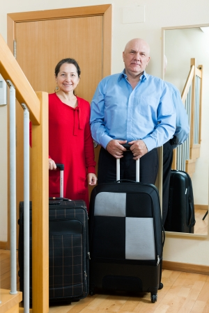 Two senior tourists with luggage near door in home photo