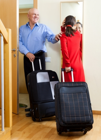 Happy mature couple with suitcases looking in mirror near door going on holiday photo