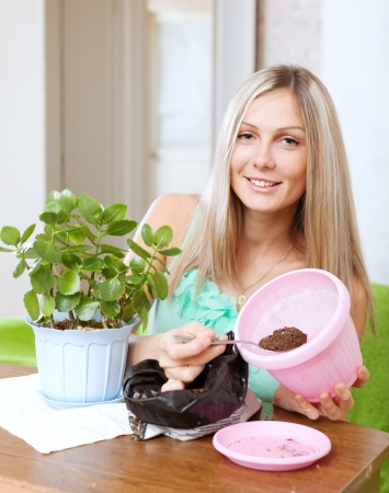 Young woman works with  flower pots at her home photo