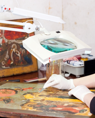 restoration: Restorer working on the ancient Christian icon with loupe at restoration workshop