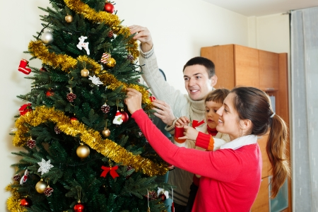 Smiling parents and child preparing for Christmas at home photo