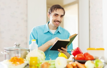 cheerful man cooking  vegetables with cookbook at kitchen photo