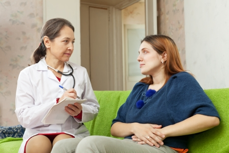 Woman complaining  to mature doctor about stitch in side  photo