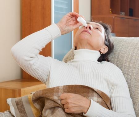 nasal drops: woman dripping nasal drops in home Stock Photo