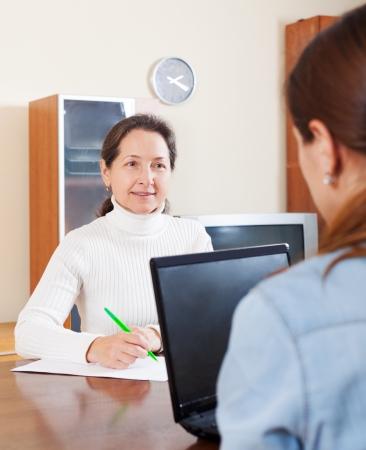 empleada domestica: Mujer madura llenar cuestionario para los empleados con el ordenador portátil del banco